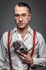Man in white shirt  holding photo camera.
