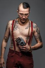 Man with naked torso holding photo camera.