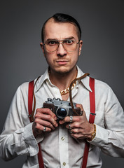 Male in white shirt holds photo camera