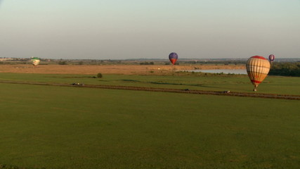 Hot air balloons landing on ground in countryside