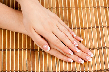 Beautiful female hands with french manicure on bamboo pad