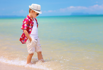 happy stylish boy walking on summer beach