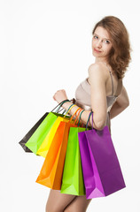 Attractive girl holding multicolored shopping paper bags