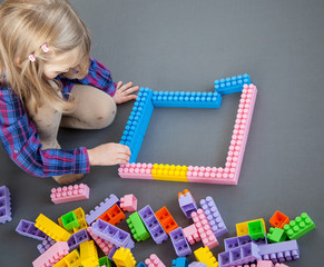 Little girl constructing with construction set