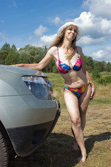 Woman in a swimsuit standing near the car