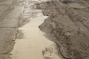 Muddy puddle on tarmac road
