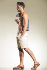 sexy casual man walking on studio background