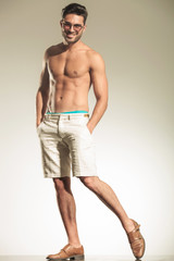 Sexy young casual man standing on studio background
