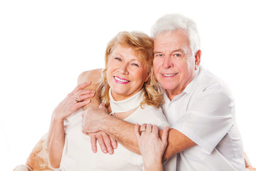 Happy mature senior couple embracing smiling at camera on white