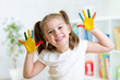 little girl with color hands in paint