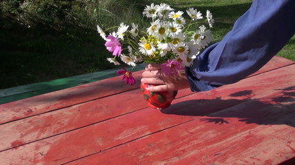 cleaning wooden table in yard and put vase with flowers