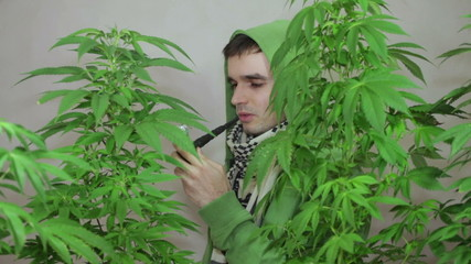 Young man in green hoodie smoking Marijuana pipe.