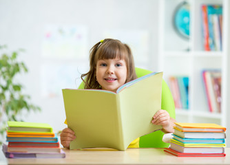 kid girl with opened book at home