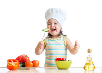 child girl in cook hat eating vegetables