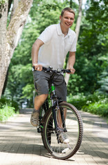 Happy young man riding on bicycle