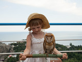 Pretty little girl holding a stick with tame owl poster