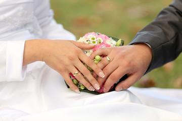 Dłonie młodej pary, obrączki i bukiet kwiatów.