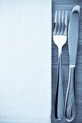 knife and fork at napkin on wood
