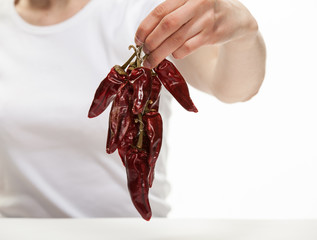 Woman's hand holding a bunch of dry red peppers