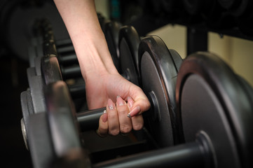 Female hand holding dumbbell
