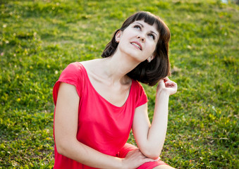 Pretty girl in red dress sitting on grass
