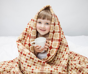 Little girl covering with a rug and holding a cup