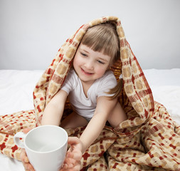 Portrait of a little girl covering with a rug
