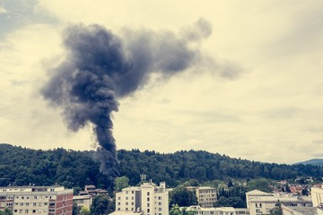 Column of black smoke rising above residential buildings.