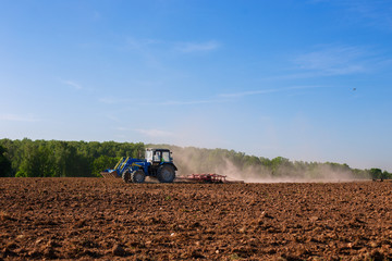 Blue tractor plowing field in spring