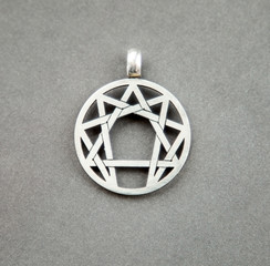 Silver symbol of enneagramma on grey background