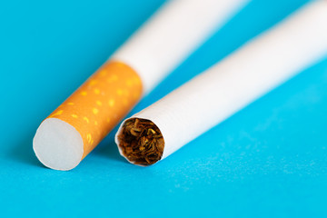 Two cigarettes on blue background