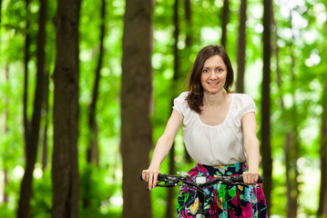 Happy young girl on bicycle in summer park