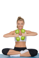 Smiling woman with dumbbells of green apples