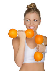 girl with weights of ripe oranges looking away