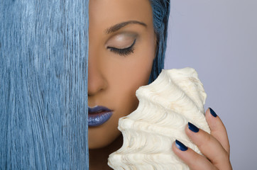 portrait of woman with long blue hair and shells