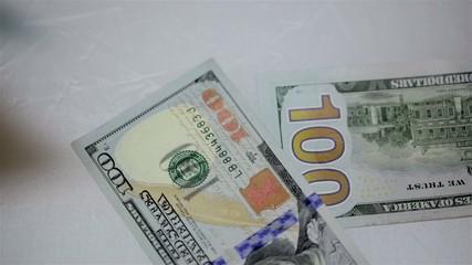 Dollars falling on white table