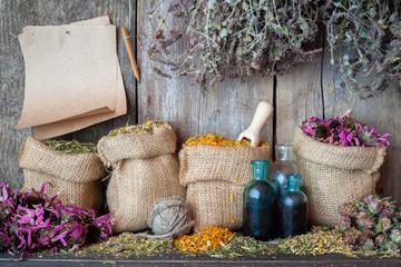 Healing herbs in hessian bags, paper sheet and bottles near wood