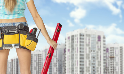 Woman in tool belt holding red building level. Buildings and sky