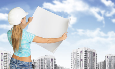 Woman in helmet holds white paper. Building and sky as backdrop