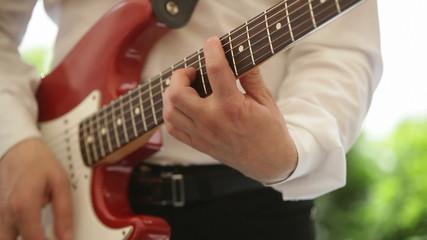 man plays electric guitar close up