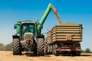 Traktor mit Ladewagen bei der Verladung von Getreide