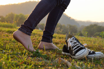 Woman take off ones sneakers and walking through a meadow with l