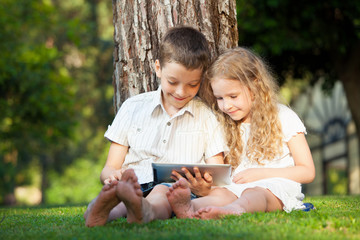 Children with tablet pc outdoors