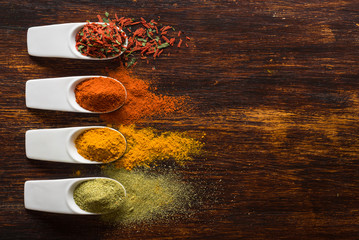 Colorful spices on brown wooden table top view