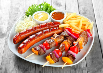 Kebab, Sausage and Fries on Plate with Sauces