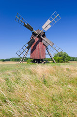 Red wooden windmill on the summer field
