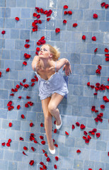 roses raining on a woman in the  pool