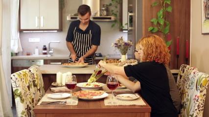 Man preparing lunch for women at home