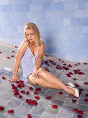 woman poses in a bed of roses in the pool