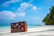 Leinwandbild Motiv Travel vintage suitcase is alone on a beach